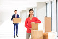 Portrait of confident mid adult businesswoman standing by stacked boxes with male colleague in background at office Royalty Free Stock Photo