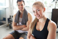 Portrait of confident woman and man in gym blond smiling sitting with arms crossed brightly lit with muscular sitting background Stock Photos