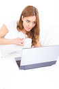 Portrait of confused and surprised woman using laptop drinking c young reading a message on screen while lying on bed at home Stock Photography