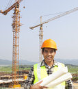 Portrait of construction worker at construction site standing under cranes Stock Photos