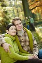 Portrait content couple sitting sunny autumn park smiling friends background Stock Images