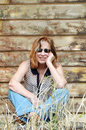 Portrait country woman with red hair leaning against timber shed Royalty Free Stock Photo