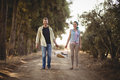 Portrait of couple carrying basket while walking on dirt road at olive farm Royalty Free Stock Photo