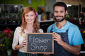 Portrait of couple holding slate with flower shop sign Royalty Free Stock Photo