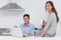 Portrait of a couple in the kitchen and using laptop Royalty Free Stock Photo