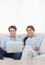 Portrait of a couple relaxing with a laptop sat on couch Royalty Free Stock Photography
