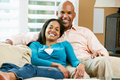 Portrait Of Couple Sitting On Sofa Together Royalty Free Stock Photos