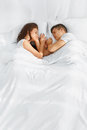 Portrait of couple sleeping in the bed young lovely on white blankets faced to each other healthy lifestyle relationships Royalty Free Stock Images