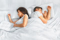 Portrait of couple sleeping in the bed young lovely on white blankets faced to each other healthy lifestyle relationships Stock Photo
