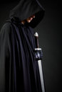 Portrait of a courageous warrior wanderer in a black cloak and sword in hand. Royalty Free Stock Photo