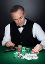 Portrait of a croupier looking at playing cards with gun and stack token chips on table Royalty Free Stock Photos