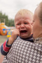 Portrait of a crying little boy who is being held