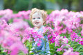 Portrait of curly baby girl with blue eyes in a field Royalty Free Stock Photo