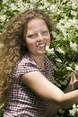 Portrait of a curly girl near jasmine flowers Stock Photos
