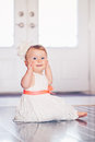 Portrait of cute adorable blonde Caucasian smiling baby child girl with blue eyes in white dress with red bow sitting on floor ind Royalty Free Stock Photo