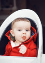 Portrait of cute adorable Caucasian little baby boy with dark black eyes sitting in high chair in kitchen Royalty Free Stock Photo