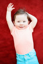 Portrait of cute adorable Caucasian smiling baby boy girl lying on floor red blanket in kids room Royalty Free Stock Photo