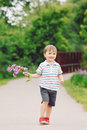 Portrait of a cute adorable funny little smiling boy toddler walking in park with lilac purple pink flowers in hands Royalty Free Stock Photo