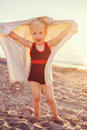 Portrait of cute adorable happy smiling toddler little girl with towel on beach making poses faces having fun Royalty Free Stock Photo