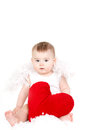 Portrait of a cute adorable little valentine angel with red soft heart isolated on white background infant girl hugging large toy Royalty Free Stock Photo