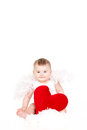 Portrait of a cute adorable little valentine angel with red soft heart isolated on white background infant girl hugging large toy Stock Photography