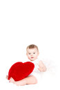 Portrait of a cute adorable little valentine angel with red soft heart isolated on white background infant girl hugging large toy Stock Photo
