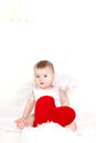 Portrait of a cute adorable little valentine angel with red soft heart isolated on white background infant girl hugging large toy Royalty Free Stock Photography