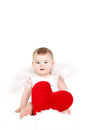 Portrait of a cute adorable little valentine angel with red soft heart isolated on white background infant girl hugging large toy Royalty Free Stock Image