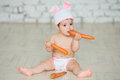 Portrait of a cute baby dressed in Easter bunny ears sitting and