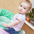 Portrait of a cute baby girl standing in chair for feeding Royalty Free Stock Photography