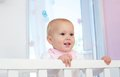 Portrait of a cute baby smiling in crib close up Stock Images