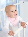 Portrait of a cute baby smiling in white crib close up Royalty Free Stock Photos