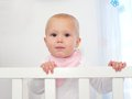 Portrait of a cute baby standing in white cot closeup Royalty Free Stock Image