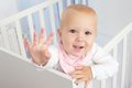 Portrait of a cute baby waving hello and smiling from crib close up Royalty Free Stock Image