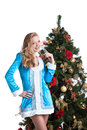 Portrait of cute blonde dressed as snow maiden posing near christmas tree Stock Images