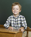 Portrait of cute boy front of a blackboard. Royalty Free Stock Photo