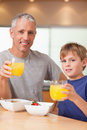 Portrait of a cute boy and his father having breakfast Stock Images