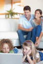 Portrait of cute children using a laptop while their parents are Stock Images
