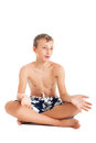 Portrait of a cute european teen boy wearing swimming shorts a boy sitting on the floor studio shot isolated on white background Royalty Free Stock Image