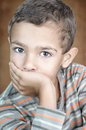 Portrait of cute litle boy covering his mouth Royalty Free Stock Photo