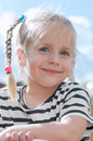 Portrait of cute little blond girl a smiling litle with hair and pigtails while she s looking into the camera Stock Photos