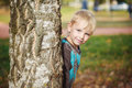 Portrait Cute little boy in a knitted sweater is playing  behind a tree in autumn park,  play at hide-and-seek Royalty Free Stock Photo