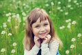 Portrait of cute little girl with beautiful smile and blue eyes sitting on the flower meadow, happy childhood concept