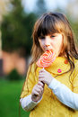Portrait of cute little girl eating big lollipop Royalty Free Stock Image