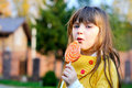 Portrait of cute little girl eating big lollipop Royalty Free Stock Photos