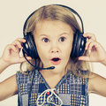 Portrait of cute little girl with headphones on her head standing near a wall Stock Photography