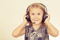 Portrait of cute little girl with headphones on her head standing near a wall Royalty Free Stock Photo