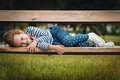 Portrait of cute little girl in a park smile lying on bench relaxing the nature Stock Image