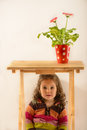 Portrait of a cute little girl sitting under the table Royalty Free Stock Photo