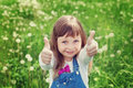 Portrait of cute little girl with thumbs up shows a class on the flower meadow, happy childhood concept, child having fun